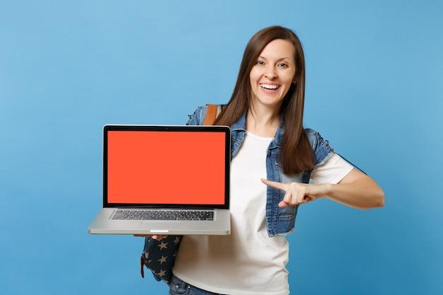 Jovem estudante de mulher alegre com mochila apontando o dedo indicador no computador laptop pc com tela vazia preta em branco isolada sobre fundo azul. educação no ensino médio. copie o espaço para anúncio.