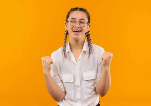 Jovem estudante de óculos com rabo de cavalo na camisa branca cerrando os punhos feliz e animada, regozijando-se com seu sucesso em pé sobre a parede laranja