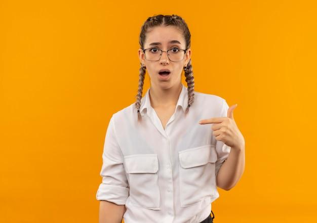Jovem estudante de óculos com rabo de cavalo na camisa branca olhando para a frente confusa, apontando para si mesma em pé sobre a parede laranja