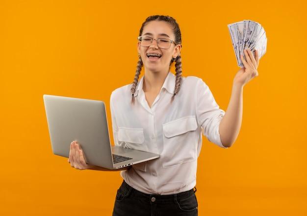 Jovem estudante de óculos com rabo de cavalo na camisa branca segurando laptop e dinheiro feliz e animada sorrindo alegremente em pé sobre a parede laranja