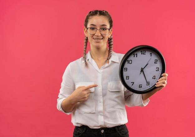 Jovem estudante de óculos com rabo de cavalo na camisa branca segurando um relógio de parede apontando com o dedo para ele, olhando para a frente sorrindo confiante em pé sobre a parede rosa