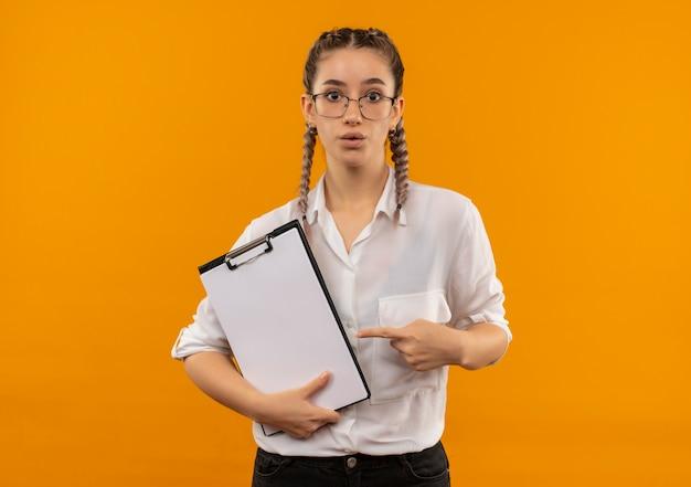 Jovem estudante de óculos com rabo de cavalo na camisa branca segurando uma prancheta, apontando com o dedo para ela, parecendo preocupada em pé sobre a parede laranja