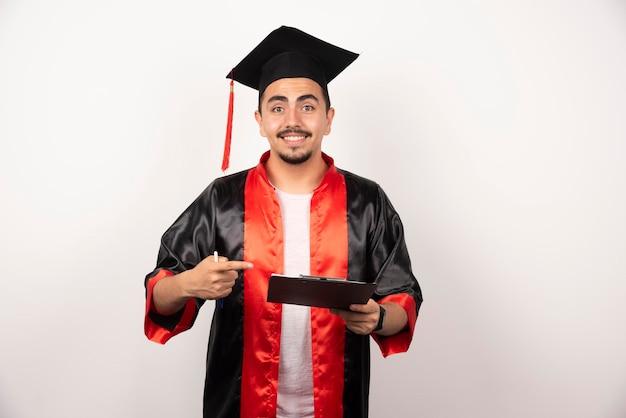 Jovem estudante de pós-graduação apontando para seu diploma em branco.