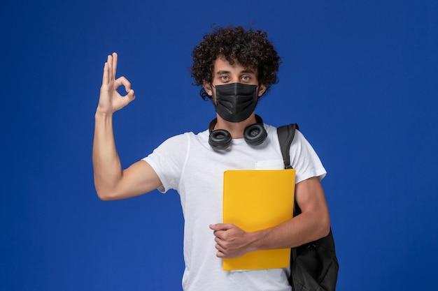 Jovem estudante do sexo masculino de vista frontal em t-shirt branca usando máscara preta e segurando arquivos amarelos sobre o fundo azul claro.