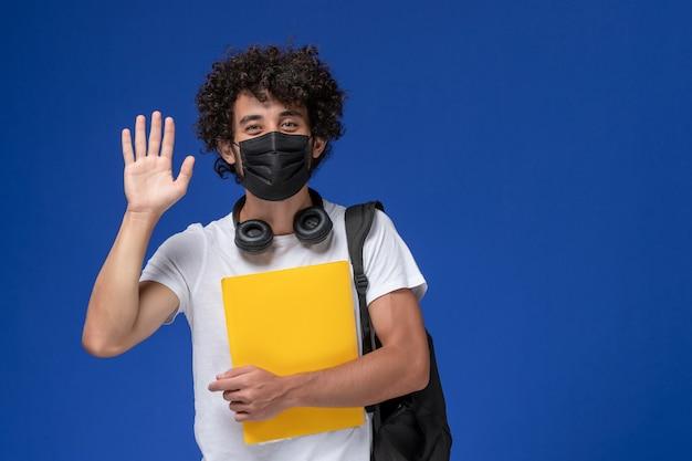 Jovem estudante do sexo masculino de vista frontal em t-shirt branca, usando máscara preta e segurando arquivos amarelos sorrindo sobre fundo azul claro.