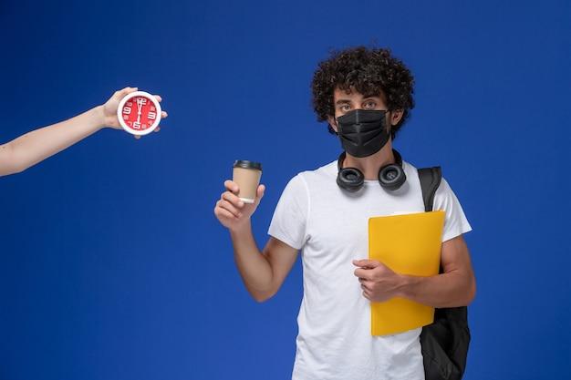 Jovem estudante do sexo masculino de vista frontal em uma camiseta branca, usando máscara preta e segurando arquivos amarelos de café sobre fundo azul.