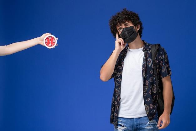 Jovem estudante do sexo masculino de vista frontal usando máscara preta com mochila e pensando sobre fundo azul claro.