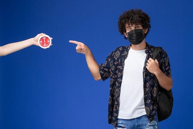 Jovem estudante do sexo masculino de vista frontal usando máscara preta com mochila em fundo azul claro.