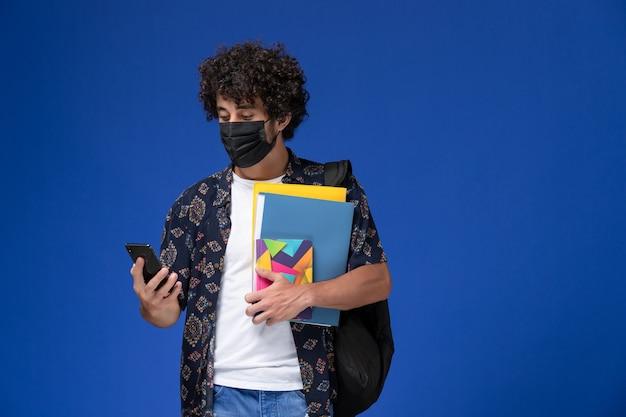 Jovem estudante do sexo masculino de vista frontal usando máscara preta com mochila segurando arquivos e telefone sobre o fundo azul.