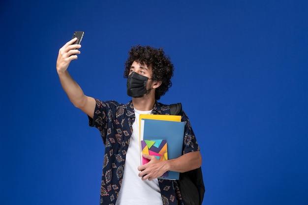 Jovem estudante do sexo masculino de vista frontal usando máscara preta com mochila segurando arquivos e tomando selfie sobre fundo azul.