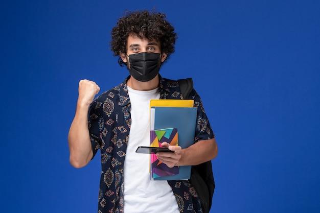 Jovem estudante do sexo masculino de vista frontal usando máscara preta com mochila segurando arquivos e usando seu telefone, regozijando-se sobre fundo azul.