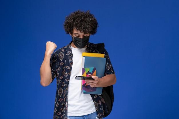 Jovem estudante do sexo masculino de vista frontal usando máscara preta com mochila segurando arquivos e usando seu telefone sobre o fundo azul.