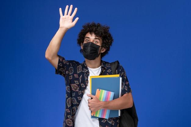 Jovem estudante do sexo masculino de vista frontal usando máscara preta com mochila segurando o caderno e arquivos acenando sobre fundo azul.