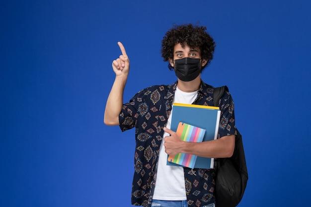 Jovem estudante do sexo masculino de vista frontal usando máscara preta com mochila segurando o caderno e arquivos sobre fundo azul.