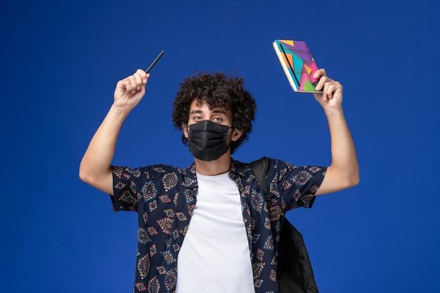 Jovem estudante do sexo masculino de vista frontal usando máscara preta com mochila segurando o caderno e uma caneta sobre o fundo azul.