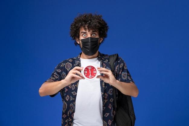Jovem estudante do sexo masculino de vista frontal usando máscara preta com mochila segurando relógios sobre fundo azul claro.