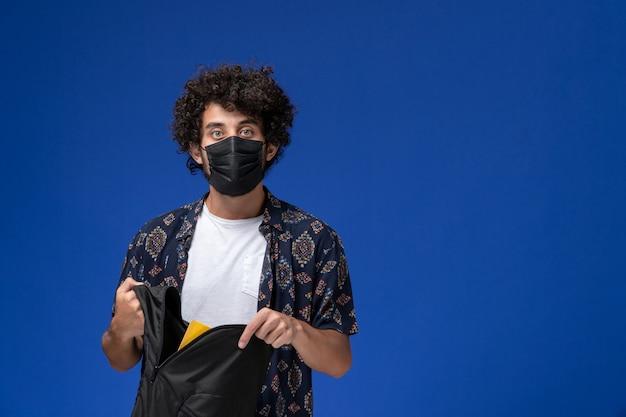 Jovem estudante do sexo masculino de vista frontal usando máscara preta e segurando a mochila preta sobre fundo azul claro.