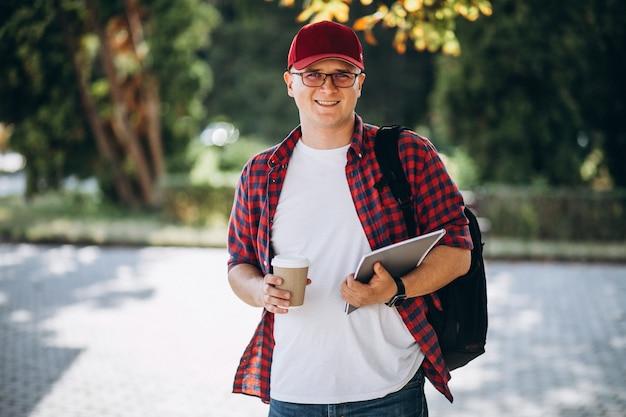 Jovem estudante do sexo masculino tomando café com o laptop no parque