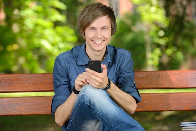 Jovem estudante do sexo masculino usando um smartphone ao ar livre no parque