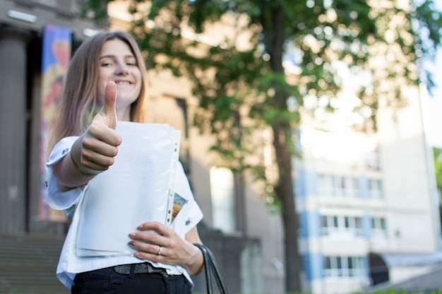 Jovem estudante em pé perto da universidade, segurando um papel nas mãos, sorrindo e mostrando como contra a faculdade, ela vai para a escola