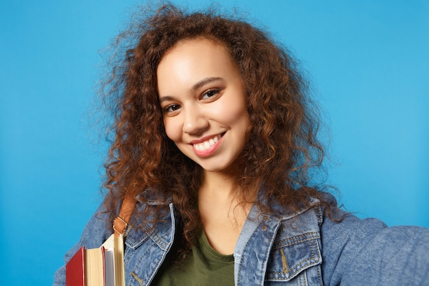 Jovem estudante em roupas jeans e mochila segura livros e faz selfie foto isolada na parede azul