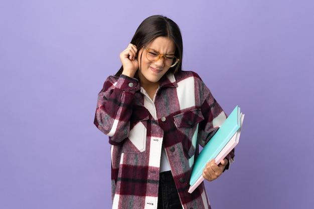 Jovem estudante em roxo frustrada e cobrindo as orelhas