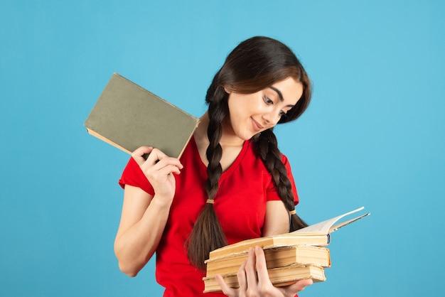 Jovem estudante em t-shirt vermelha, lendo um nome de um livro na parede azul.