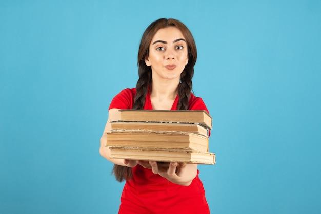 Jovem estudante em t-shirt vermelha, oferecendo livros na parede azul.