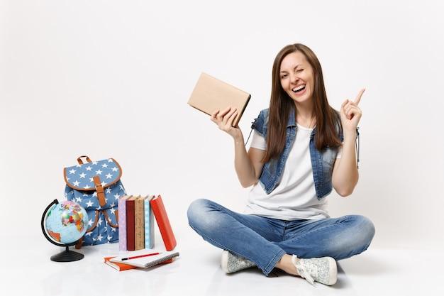 Jovem estudante engraçada em roupas jeans segura um livro apontando o dedo indicador para cima e piscando, sente-se perto do globo, mochila, livros escolares isolados