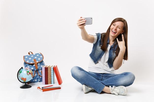 Jovem estudante engraçada fazendo selfie tiro no celular, mostrando sinal de rock-n-roll piscando perto da mochila de livros escolares do globo