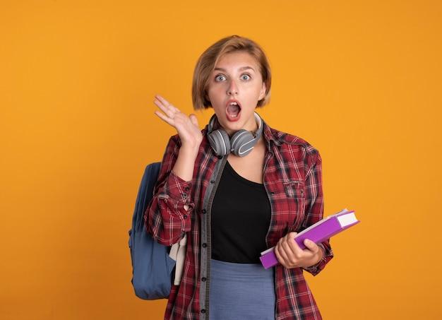 Jovem estudante eslava chocada com fones de ouvido usando suportes para mochila, livro e caderno levantados