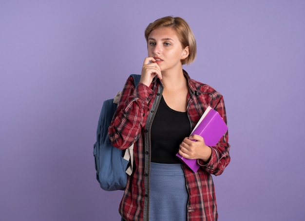 Jovem estudante eslava confusa usando mochila morde unha segura livro e caderno