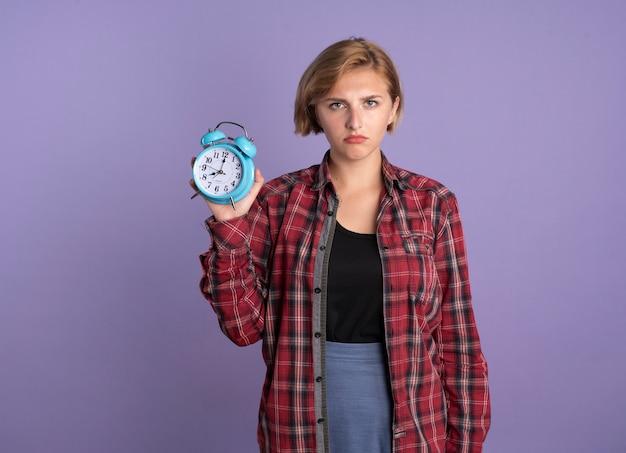 Jovem estudante eslava decepcionada segurando um despertador