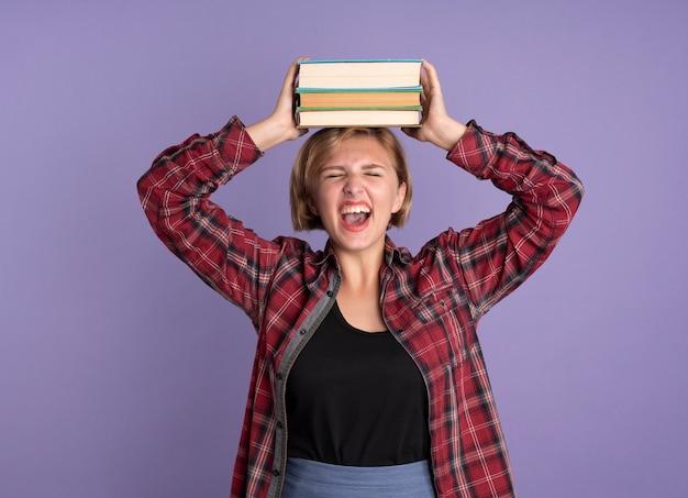 Jovem estudante eslava irritada segurando livros na cabeça