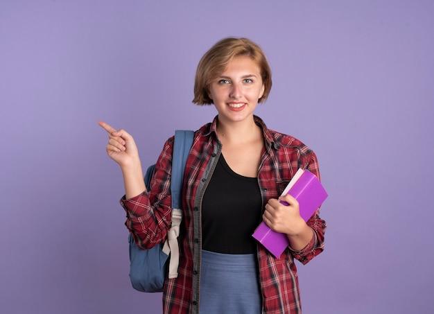Jovem estudante eslava sorridente usando uma mochila segurando o livro e o caderno ao lado