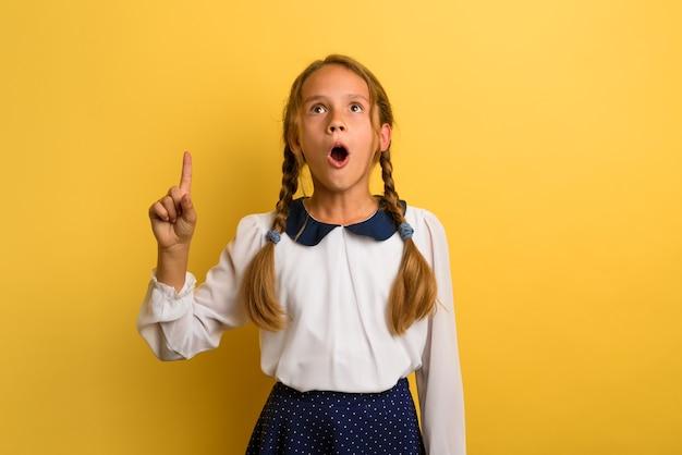 Jovem estudante está com expressão chocada e indica algo. fundo amarelo