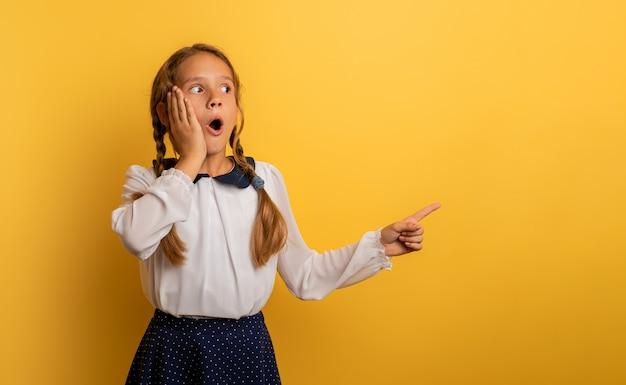 Jovem estudante está com expressão chocada e indica algo