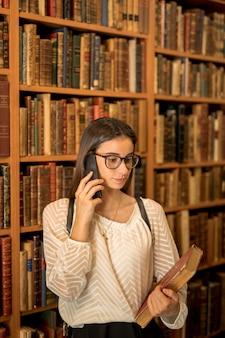 Jovem estudante falando no telefone na biblioteca