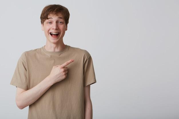 Jovem estudante feliz usa camiseta bege indica com o dedo no espaço da cópia. isolado sobre a parede branca. jovem aponta com o dedo para o lado direito