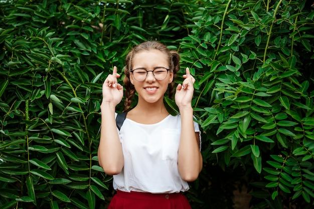 Jovem estudante feminino bonito em copos esperando, posando sobre folhas ao ar livre.