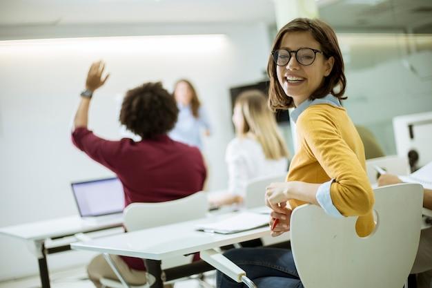 Jovem estudante feminino com óculos na sala de aula