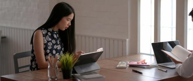 Jovem estudante feminino, concentrando-se em sua tarefa na biblioteca
