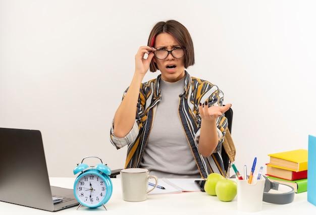 Jovem estudante furiosa usando óculos, sentada na mesa, segurando os óculos e mostrando a mão vazia, isolada no branco
