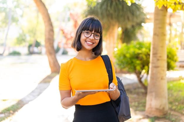 Jovem estudante ganha um parque segurando um tablet