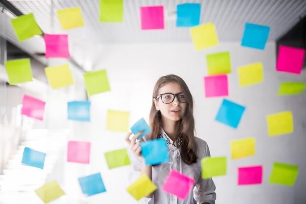 Jovem estudante garota de negócios em óculos assistir na parede transparente com muitos adesivos de papel nela