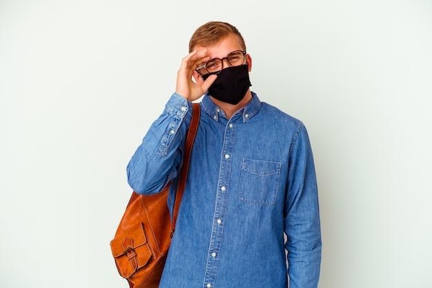 Jovem estudante homem caucasiano estudando alemão isolado no branco animado, mantendo o gesto ok no olho.