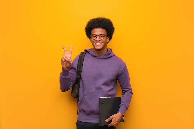 Jovem estudante homem divertido e feliz, fazendo um gesto de vitória