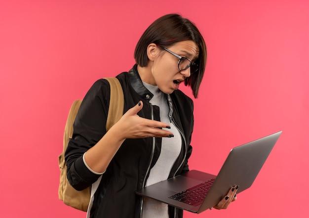 Jovem estudante impressionada de óculos e bolsa traseira segurando e olhando para o laptop, mantendo a mão no ar isolada no rosa