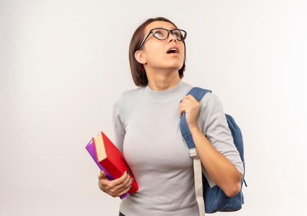 Jovem estudante impressionada de óculos e bolsa traseira segurando livros olhando para cima isolados no branco