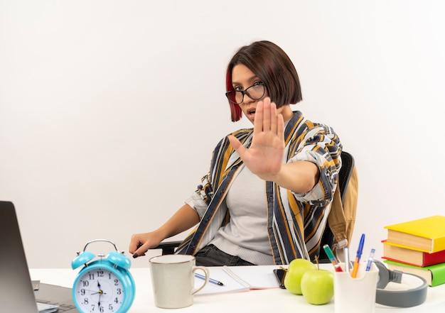 Jovem estudante insatisfeita de óculos, sentada na mesa com ferramentas da universidade, gesticulando para parar na câmera, isolada no fundo branco